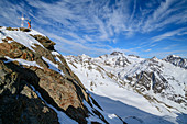 Woman on ski tour stands on the rocky summit of Plereskopf, Plereskopf, Matscher Valley, Ötztal Alps, South Tyrol, Italy