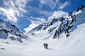 Three people on ski tour ascend through valley, Pangert, Tux Alps, Tyrol, Austria