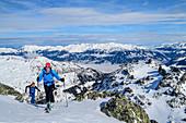 Frau und Mann auf Skitour steigen zum Pangert auf, Kitzbüheler Alpen im Hintergrund, Pangert, Tuxer Alpen, Tirol, Österreich