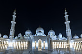 Front view of the illuminated Sheikh Zayid Mosque in Abu Dhabi, UAE