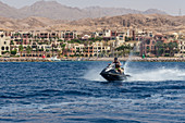 Tourist drives jet ski Tala Bay, Jordan