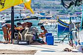 Fishermen wash themselves at the port of Marsaxlokk, Malta