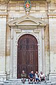 Men sit in front of the church in Rabat, Malta