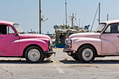 Two old cars at the port of Marsaxlokk, Malta