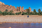 Two local women walk in front of the city of Ait Ben Haddou, Morocco