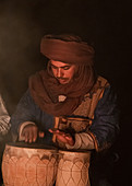 Berber makes music in the evening around the campfire in Erg Chebbi, Sahara, Morocco