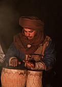 Berber musiziert am Abend am Lagerfeuer in der Erg Chebbi, Sahara, Marokko