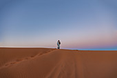 Berber stands on a dune in the Erg Chebbi desert in the Sahara, Morocco, early in the morning