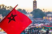 Die marokkanische Flagge weht über dem Djemaa El Fna in Marrakesch, Marokko