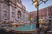 Tourist stands in front of the Trevi Fontana in Rome, Italy early in the morning