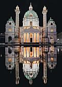 Nächtlicher Blick auf die beleuchtete Karlskirche in Wien, Österreich