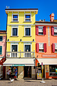 Shop and colorful house facades in Caorle, Veneto, Italy