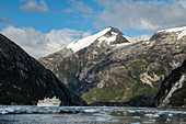 While the passengers enjoy the trip with a Zodiac rubber dinghy along the glacier, the expedition cruise ship MS Bremen (Hapag-Lloyd Cruises) is surrounded by mountains at anchor, Garibaldi glacier, near Beagle Canal, Alberto de Agostini National Park, Magallanes y de la Antartica Chilena, Patagonia, Chile, South America