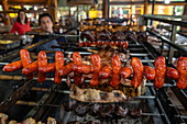 Sausages (chorizo) and other meat are grilled on rotating skewers in a restaurant, Puerto Montt, Los Lagos, Patagonia, Chile, South America