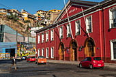 The dark red customs building is located near one of the many funiculars in the hilly city, Valparaiso, Valparaiso, Chile, South America