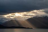 Light rays in the late afternoon break through a heavy cloud cover over a scene of mountains and calm sea, near Pio XI glacier, Magallanes y de la Antartica Chilena, Patagonia, Chile, South America