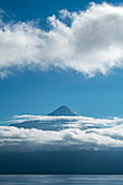 The cone of the majestic volcano Osorno on Lake Llanquihue rises above thin clouds, near Puerto Montt, Los Lagos, Patagonia, Chile, South America