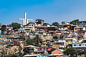 Dense, colorful houses on a slope with a monumental cross, La Serena, Coquimbo, Chile, South America