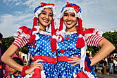 Two beautiful young women in colorful costumes pause from celebrations in Plaza de Armas, Trujillo, La Libertad, Peru, South America