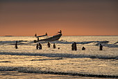 Fishermen waist-deep in the water work with a small boat to spread their net, Manta, Manabi, Ecuador, South America