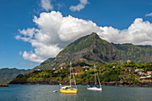 Two sailing boats are moored in the sun in front of a massive mountain, Atuona, Hiva Oa, Marquesas Islands, French Polynesia, South Pacific