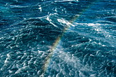 Seen from the deck of an expedition cruise ship, rainbow over the ocean forms near Stewart Island, New Zealand on a bright windy day