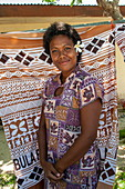 A smiling young woman with a frangipani (plumeria) flower in her hair stands in front of patterned pieces of fabric that she sells to visiting tourists from an expedition cruise ship, Mamanuca Islands, Fiji, South Pacific