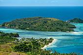 Panoramablick auf kleine Siedlung, zwei Inseln, den Ozean und Riffe in zahlreichen Blau- und Grüntönen, Mamanuca Islands, Fidschi-Inseln, Südpazifik