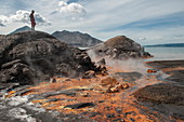 A young man stands on rocks and looks at orange residue and hot springs near an active volcano, Rabaul, East New Britain Province, Papua New Guinea, South Pacific