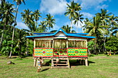 Two people enter a Selzen house with bright colors and patterns in a grassy landscape surrounded by palm trees, Garove Island, Vitu Islands, West New Britain Province, Papua New Guinea, South Pacific