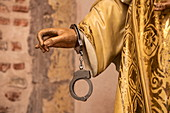 A pair of handcuffs hangs on the wrist of a statue, symbolizing aid to detained believers in Panama City, Panama, Central America