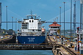 A cargo ship waits in the Gatun locks in the Panama Canal with the Atlantic Bridge in the background, near Panama City, Panama, Central America