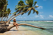A woman in a bikini holds her hat while sitting on the trunk of a palm tree on a narrow, sunny beach, San Blas Islands, Panama, Caribbean