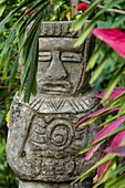 A stone figure representing a person is surrounded by palm fronds and leaves, Santa Marta, Magdalena, Colombia, Caribbean