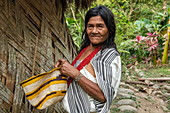 A woman holding a handmade basket is standing next to her hut, Santa Marta, Magdalena, Colombia, Caribbean