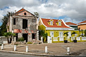 A derelict, derelict building contrasts with its bright, recently restored neighbor on the right, Willemstad, Curacao, Netherlands Antilles, Caribbean