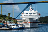 The expedition cruise ship MS Bremen (Hapag-Lloyd Cruises) outshines other boats on the pier, Willemstad, Curaçao, Netherlands Antilles, Caribbean