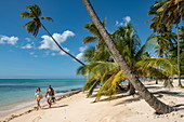 Two people run along a white sandy beach lined with palm trees, Pigeon Point, Tobago, Trinidad and Tobago, Caribbean