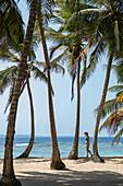 Eine Frau mit Sonnenschutz geht zwischen Kokospalmen entlang einem Strand, Isla Aroma, San Blas Inseln, Panama, Karibik