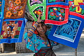 A Guna (formerly Kuna) native woman stands in front of colorful handmade Molas textiles that she sells to tourists, Isla Aroma, San Blas Islands, Panama, Caribbean
