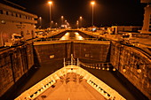 Night view of the bow of an expedition ship in one of the Miraflores locks in the Panama Canal, near Panama City, Panama, Central America