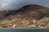 View of dilapidated buildings at the foot of rolling hills outside the former coal mining town, Pyramiden, Billefjord, Spitsbergen, Norway, Europe