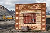An unused building stands opposite the runway for the former mining town of Pyramiden, Billefjord, Spitsbergen, Norway, Europe