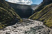 A river flows from a high waterfall between steep slopes to the ocean just a hundred meters away, Flintholmen, Spitsbergen, Norway, Europe