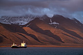 The late evening sun (after 9 p.m.) paints a special scene when a ship passes barren, reddish mountains brushed by clouds and dusted with snow, Longyearbyen, Spitsbergen, Norway, Europe