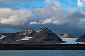 A typical landscape with barren, rugged mountains dusted with snow and a retreating glacier, Ny-Ålesund, Spitsbergen, Norway, Europe
