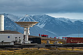 NASA's satellite antenna points to the sky as passengers of the expedition ship Sea Spirit (Poseidon Expeditions) gather for a tour of the research facility, Ny-Ålesund, Spitsbergen, Norway, Europe