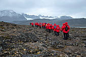 Passengers on the expedition cruise ship MS Sea Spirit (Poseidon Expeditions) begin a hike across rocky ground, Signehamna, Albert I Land, Svalbard, Norway, Europe