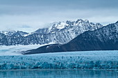 Graphic scene of rugged, snow-capped mountains and a wide glacier that stretches to the sea, Lilliehöökfjord, Albert I Land, Spitsbergen, Norway, Europe