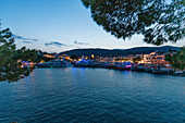 Nocturnal view of the illuminated port and boats of Skiathos, Greece